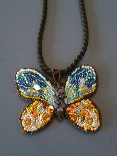 Colgante mariposa hecho a mano con microperlas bordadas sobre fieltro.