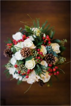 A perfect bouquet for a winter wedding, with white roses, pinecones, red cranberries, and hints of evergreen - beautifully crafted by TWIGS Greenville. Photo by Hannah Woodard // www.hannahwoodardphotography.com