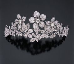 """A DIAMOND TIARA, late 1800's. In the garland style, three old mine-cut and rose-cut diamond """"en tremblant"""" flowerheads set above a rose-cut and old mine-cut diamond flower spray; with extra fittings to be worn as three brooches. (Christie's)"""