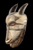 """Luba - since the mid-1980's some variations on the typical """"kifwebe"""" masks appeared. Some obvious animal references were added to the classic rectangular box-shape. Some had horns curving downward for a ram, or upward for an antelope, or backward for a goat. Some had large ears flanking the forehead as a jackal. Some of these zoomorphic """"bifwebe"""" were more colorful than the classical white and black Luba """"bifwebe"""". Sometimes blue, green or yellow were added. This developement continued…"""
