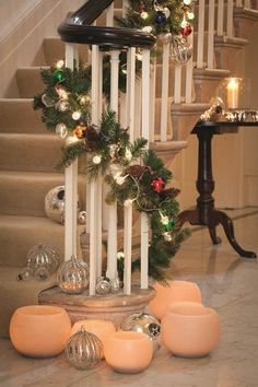 Sarah Raven's fantastic Christmas bannister idea, with a pine garland sweeping up the stairs and filled with baubles and lights.