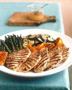 Boneless, skinless chicken breasts are pounded thin with a meat tenderizer for quick cooking and then marinated in a piquant mix of orange and lemon juices, Dijon mustard, and sesame oil for an hour or two. They can be grilled at the same time as the asparagus and zucchini.
