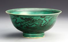 China, green glazed footed bowl decorated with dark-hued figures of serpentine dragons with four claws, and auspicious symbols. Height 3 1/4 in., Diameter 7 in.