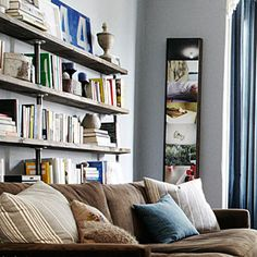 Using plumbing parts and lumber, this renter built an industrial-style bookcase for the narrow space behind the living room sofa. Since the piece is on casters, it can easily move out whenever he does.