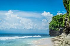 Am incredibly beautiful view of an ocean tropical beach with blue sky, white clouds and cliffs, Indonesia