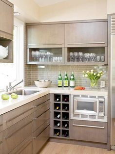 drink station with a storage configuration that is convenient and attractive. The upper cabinets are divided into two portions: garage-style drawers conceal less frequently used items above, while open shelves display drinkware for easy accessibility. Square cubbies below store wine bottles.