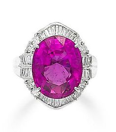 A rubellite tourmaline and diamond ring Set with an oval-cut rubellite tourmaline, within an undulating surround of baguette and round brilliant-cut diamonds, mounted in platinum, the rubellite tourmaline estimated to weigh approximately 11.80 carats, the diamonds estimated to weigh approximately 0.80 carats