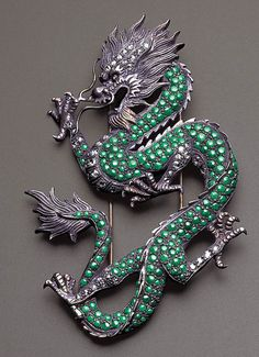AN UNUSUAL JADEITE AND DIAMOND DRAGON BROOCH    Designed as a fierce ascending dragon with finely modelled details, its sinuous body set throughout with chrome-jadeite cabochons to the rose-cut diamond-set belly, legs and horns, mounted in silver and 18K yellow gold, 9.5 cm.