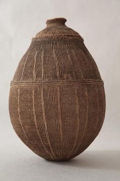 An old Turkhana jar made of twisted cord in a vertical pattern covered with hardened clay and a fitted lid. Tribal Art.