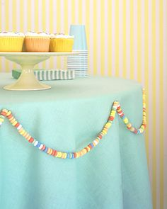 cool table border-Candy Necklace Trim  A party table draped in candy -- what could be sweeter? To make a sugary swag, cut through the elastics of candy necklaces, and remove a few rings from each end. Tie necklaces together to make a circle that will reach around your table. Attach to tablecloth with safety pins, securing from underneath.