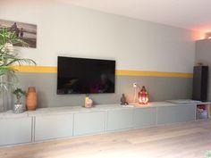 Lange lage kast van gepimpte Ikea Besta kastjes met steigerhout . Geel en grijs op de muur.