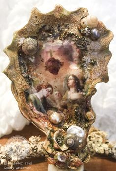 """Angels and spiritual ephemera are very dear to me and usually inspire my  creative journey.  I love the Relics &Artifacts® Coquille set and find that the oyster shell  is a beautiful substrate to work in miniature.  My inspiration started with a inkjet printed copy of this beautiful image  of the Madonna and two angels. My design style is spontaneous while using  many layered mediums, materials and techniques while striving to replicate  in an """"old world"""" and """"time worn"""" fashion.  """"We are…"""