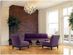 Purple looks really nice against brown brick. Maybe do a purple couch (or another rich pop of color) and make your bed a neutral color. Keep the focus in the living room