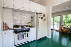 Green floors and white subway tile in bright kitchen