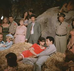 """""""Kissin' Cousins"""" movie still: Full shot of haystack containing Cynthia Pepper as Corporal Midge Riley, Yvonne Craig as Azalea Tatum, and Elvis Presley as Josh Morgan, watched by Arthur O'Connell as Pappy Tatum, Glenda Farrell as Ma Tatum, and Donald Woods as General Alvin Donford. Pictured: 