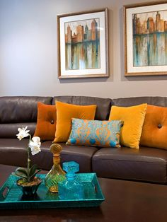 A brown leather sofa matches a dark wooden coffee table in front of the neutral living room walls. Orange throw pillows and a contrasting patterned blue pillow add color to the room. Two scenic photos and a bright blue breakfast tray pull repeat the hue.