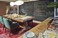Sala de jantar para Adir Sodré - Ivan Guimarães Inspirado em chefs de cozinha, o profissional pintou, na sala de jantar, uma das paredes com tinta de lousa, para a anotação de receitas . As demais ganham obras de arte de Adir Sodré, inspiradas em Frida Kahlo, ponto de partida para a escolha das cores fortes e a abundância de madeira na decoração.