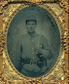 Armed Confederate  1/9 plate tintype  of a private wearing an 1855 rifleman's belt  and holding his saber bayonet proudly in the  air.