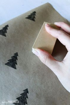Hand stamping black Christmas tree on sheet of brown kraft paper for DIY wrapping paper - This is so fun! Love the Silhouette Mint machine #Silhouette #Mint #WrappingPaper #Stamp #ChristmasTree