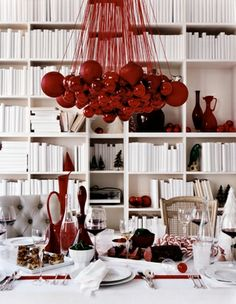 Christmas in red + white from Escapade.  Love the red ornament chandelier.  Simple white table cloth with stripes of red ribbon criss-crossed to make look like a wrapped Christmas package.