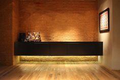 O hall de entrada tem parede de tijolo aparente + buffet preto com iluminação embutida.