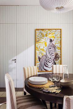 Comedor diario de la casa de María Freytes con mesa circular de madera (Didot), sillas (Jazmeen Deco) tapizadas con género rayado (Agustina Lanusse) y cuadro de cebra (Paula Arocena) sobre una pared revestida con machimbre blanco.