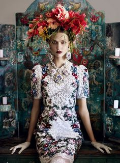 "Vogue's newly released editorial features a a modern figure of striking resemblance to the renowned Mexican painter, Frida Kahlo.  Vogue's ""Frida"" poses in from of an antique style painted wood candelabra screen, poised perfectly in a lace floral dress, donned in an exaggerated version of the artist's signature floral headdress, accessorised by oversized drop earrings and a necklace, each a bouquet of roses backed with lace and garnished with pearls.//""Frida"" de…"