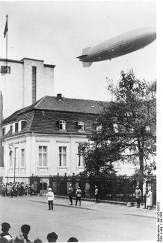 """Juli 1936: Zeppelin LZ 129 """"Hindenburg"""" über der Reichskanzlei bei einem Werbeflug zu den Olympischen Sommerspielen 1936. Im Hintergrund der 1928–1930 errichtete Erweiterungsbau"""