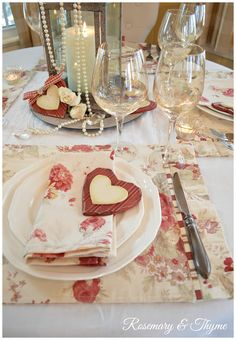 A lovely Valentine's Day tablescape.  The matching placemat and napkin is the major mood maker, along with an interesting centerpiece of lantern containing a candle, draped with pearls, and graced with a valentine like that on the plate (which looks like a cookie). Everything else is simple, clean, and plain.