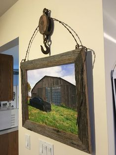 An old barn pulley some barb wire & barn wood and there you have it a rustic picture frame
