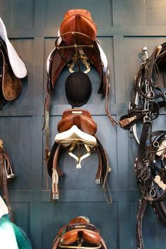 Saddles on their racks in the tack room.