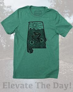 Alabama home shirt with mountain bike style by Milostees- Graphic illustration of a cyclist riding Tannehill bike park for an epic ride. Hand screen printed image on soft blue shirt in a cotton, polyester blend that is perfect for watching the Crimson Tide or cycling adventures in the Heart of Dixie! Elevate the day wear a more comfortable you! $21.99, free shipping in the USA. #AlabamaShirt #HeartOfDixie