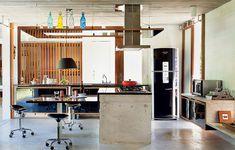 A casa de praia tem cozinha aberta e bem ventilada, com bancada ampla para comer e preparar receitas. Projeto do escritório Brasil Arquitetura. Banquetas com rodízios são uma boa escolha!