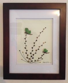Genuine green sea glass and beach pebbles collected from a beach on the central coast of California southern end of Bug Sur, arranged in a collage of dragonflies on foliage blowing in the wind. Matte is 8x10 in a 16x13 chocolate brown wood frame.