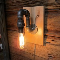 Black Pipe Wall Sconce Light on maple wood mounting by ParisEnvy Wood Sconce, Wall Sconce Lighting, Wall Sconces, Bathroom Lighting, Pulley Light, Driftwood Wall Art, Minimalist Home Decor, Pipe Lamp, Unique Lamps