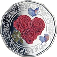This decorative 2011 silver collectible coin from the Cook Islands features brightly-colored roses and blue birds.