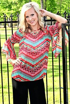 Printed blouse with bell sleeves. Can also be worn off the shoulders. Brittani is wearing a size Small.