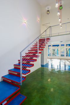 Entry with floating staircase, stained concrete floors, inlaid steps and unique custom lighting.