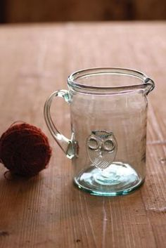 """Add some flair to your summer get-togethers with this chic, hand blown recycled glass pitcher with a quirky owl on the front. Handcrafted in Colombia. 5""""d x 8""""t $59"""