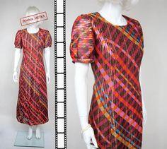 Błyszcząca maxi sukienka w stylu orientalnym. Krój lekko poszerzany, rękawy krótkie. Sukienka wzorzysta w pionowe złote błyszczące pasy - efekt piorunujący. Ma podszewkę. Wykonana z lekkiej tkaniny syntetycznej.   wymiary mierzone na płasko (+/- 1 cm)   szerokość pod pachami - 50 cm x 2  pas - 48 cm x 2  biodra - 62 cm x 2  długość od ramienia do dołu - 136 cm