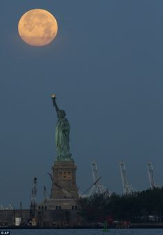 The supermoon sets over the Statue of Liberty, N.Y. Sunday, June 23, 2013  The word supermoon was coined in 1979 by astrologer Richard Nolle, who used the term to describe a new or full moon that occurs when the moon is at or near its closest approach to Earth.  While this supermoon, which rose in the east yesterday, is spectacular, an even larger one is expected on September 28, 2015.  And the largest supermoon until 2034 will roll in on November 14, 2016.