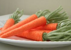 Yarn wrapped around a paper cone that is lightly covered with white glue.  Green yarn is bunched and tied and then glued inside.  A wire in inserted in the green to form an eye to hang the carrot.