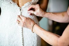 Beautiful detail shot of the Mother of the Bride buttoning up the wedding dress on wedding day / Lace bridal gown / LEB is weekend wedding destination & barn event venue located in the Texas Hill Country / Photo: J. Violet Photography