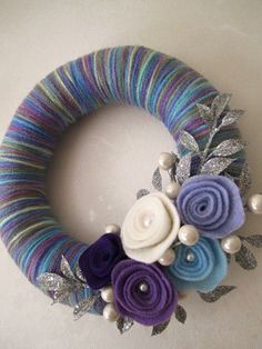 8 inch straw wreath wrapped in purple/ blue mixed color yarn, decorated with felt roses, pearls, and glitter silver leaves. No instructions, just ideas! Crafty Home Decor Diy Yarn Wreath, Crochet Wreath, Felt Flower Wreaths, Straw Wreath, Felt Wreath, Wreath Crafts, Felt Crafts, Yarn Wreaths, Door Wreaths
