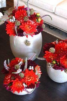 red flowers in white vases