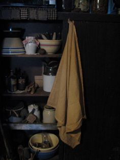 Primitive Cupboard filled with early goods and hanging aged pantry cloth.