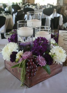 Table centerpiece design featuring florals, fruits, and floating candles
