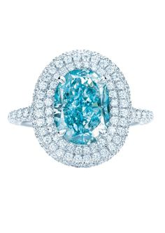 Blue diamond engagement rings: the rarest of them all.  Tiffany & Co. double Halo blue diamond engagement ring encircled by pavé diamonds.