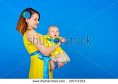 Mother and daughter wearing the same yellow dress. Happy mother holding her daughter in her arms. The concept of the joy of family life. Family Stock Photo, Happy Mothers, Yellow Dress, Family Life, Hold On, Arms, Daughter, Joy, Concept