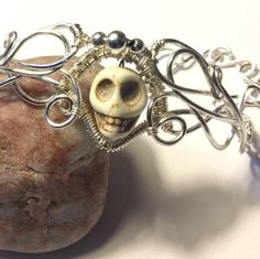 Silver cuff bracelet wire wrapped with a center white skull bead. I used 26 and 18 gauge wire non tarnish. Skull bead is Nice bracelet for Halloween. Halloween Jewelry, Halloween Skull, Skull Bracelet, Cuff Bracelets, Handmade Wire Jewelry, Unique Jewelry, Wire Wrapped Bracelet, Beaded Skull, Gothic Jewelry